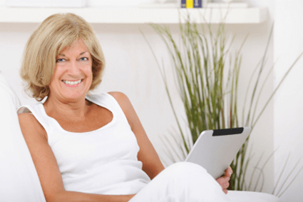 Woman sitting on the lounge with her tablet.